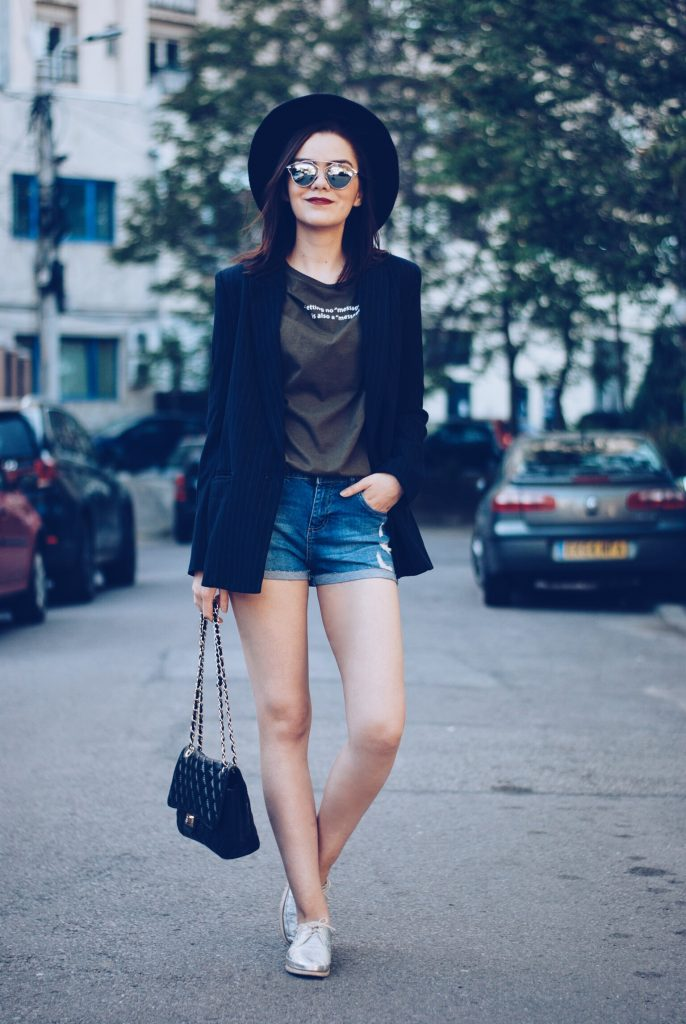 Black hat, khaki shirt, pinstripe blazer, so real sunglasses, denim shorts, silver metallic shoes, black leather bag, spring outfit by Andreea Birsan