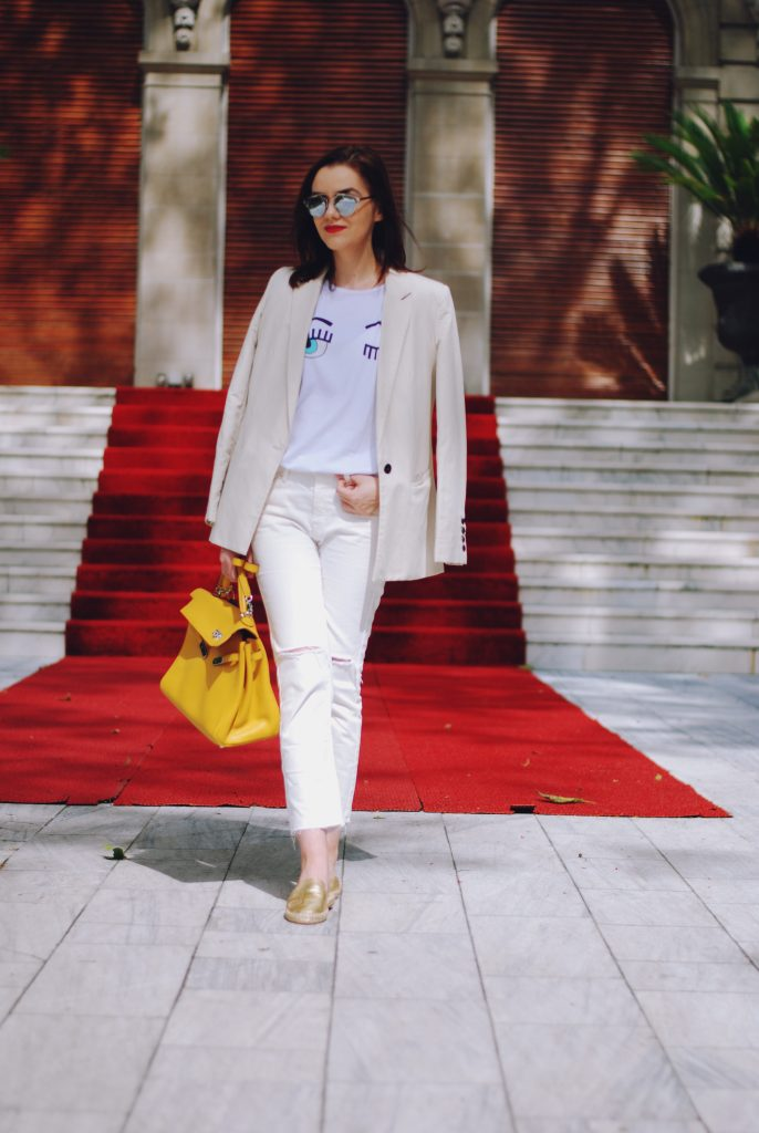 White flirty tshirt, cream blazer, white distressed cropped flared jeans, gold metallic flat mules, yellow bag, christian dior sunglasses, cute summer outfit, summer trends by Andreea Birsan