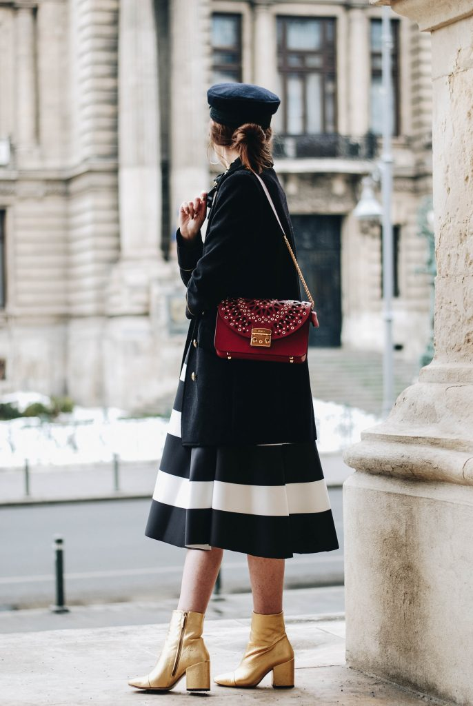 Valentine's day outfit idea for women, striped midi skirt, bershka metallica t-shirt, rock band tee, graphic tee, mango gold metallic ankle boots, furla red metropolis shoulder bag, mejuri gold jewelry, silver hoop earrings, cute winter outfit, casual winter look, pinterest outfit for women, tumblr outfit, tumblr girls, winter fashion trends, fashionista, how to wear a midi skirt, andreea birsan, couturezilla, french knotted scarf, chic on a budget, tommy hilfiger x gigi hadid military cap, hat, double breasted woolen military coat, zara coat, asos, topshop, how to wear a midi skirt with a t-shirt, top