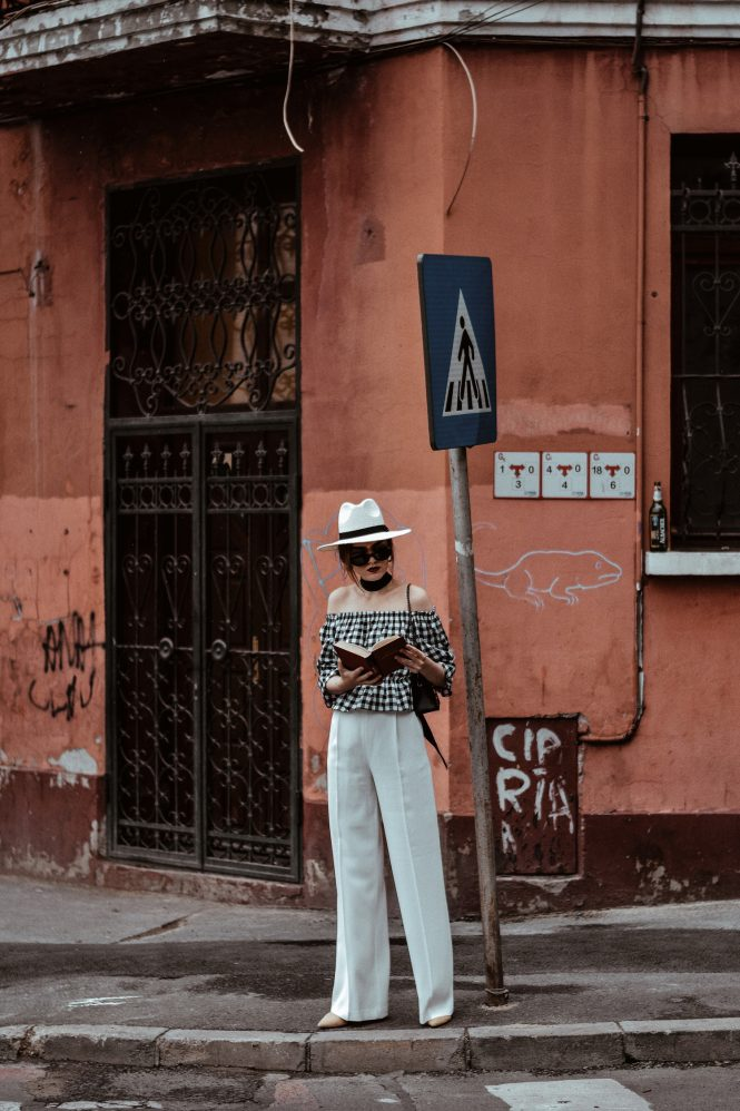 Zara white wide leg pants, crepe trousers, white palazzo pants, french women, fashion editorial, white trousers, what pants to wear in summer, what to wear when it's too hot, european summer outfits, asos gingham off shoulder gingham top, ots top, off the shoulder blouse, gingham, check print, vichy top, bardot gingham top, chicwish crop top, h&m ruffled top, frill, mango ruffle summer top, forever 21 cutest summer outfit for girls, what to wear when traveling, traveler outfit, havana, cuba, urban outfitters white straw hat, white and black outfit for summer 2017, river island fedora hat, topshop suede beige pumps, black mini bag, micro bag trend, black leather furla metropolis bag, new collection, fashion, leather crossbody bag, vintage reclaimed round black sunglasses, skinny scarf, neck scarf, how to look parisian, italiana, black skinny scarf, book, reading list, what to read, andreea birasn, couturezilla, sterling silver hoop earrings, silver, jewelry, statement earrings, vintage earrings, vintage inspired, american style, european summer outfit 2017, uk fashion blogger, united kingdom fashion blogger, fashionista, women with style, chic outfit ideas for women 2017, ootd, outfit inspiration, outfit of the day, cute pinterest outfit for women, minimal outfit inspo, girl, girls, women, cool kids, girls of tumblr, photos, european fashion blogger, european fashion blog, uk blog, fashion trends for summer 2017, how to wear the wide leg pants trend, palazzo pants what to wear them with, chic on a budget, zara outfit, styling tips and hacks, how to look parisian chic, casual outfit for women on holiday, how to wear gingham, print, red lipstick sephora, matte, erborian foundation, suede mules, nude mules, beige mules, pointy toe shoes, how to wear mules, instagram andreea birsan, style inspiration, inspo, summer in europe