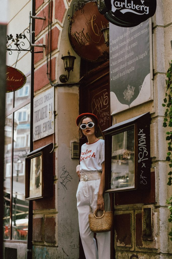 Mango white high waisted trousers, topshop paperbag trousers, all white summer outfit, peg trousers, crisp white trousers, tailored trousers, sleek suit trousers, suit pants, how to pull off the high waist trousers trend, belt, zara color block t-shirt, retro pannel tee, printed tee, slogan tee, tshirt, white shirt, how to wear all white with pops of red, how to pull off an all white outfit, what to wear with red, public desire red pearled sandals, red strappy sandals, velvet sandals, pearl embellished red sandals, the pearl shoes trend, everything pearled, asos straw bag, cutest basket bag, raffia bag, wicker bag trend, the best bags for summer, micro bag trend, mini straw bag, small straw bag, where to find the best straw bags, the blogger approved straw bags, beach bags, red beret, how to wear a beret and look like a parisian, white oval sunglasses, nirvana sunnies, kurt cobain white sunglasses, sunnies, silver hoop earrings, jewelry, how to dress in white and red, andreea birsan, couturezilla, cute summer outfit ideas 2017, the summer bag that is all over instagram, popular bag, trending, best fashion ideas, styling, how to look Parisian chic, European summer street style inspiration for women 2017, pinterest chic outfit ideas for woman, summer outfit ideas, summer ootd inspiration, outfit of the day, ootd, fashion icon, style inspiration, fashionista, fashion inspiration, style inspo, what to wear in summer, how to look French, chic on a budget, zara outfit, mango, topshop, asos, river island, forever 21, urban outfitters, how to mix high end pieces with luxury ones, zara and Gucci, how to look chic when not wearing a dress, outfit alternatives for summer, tomboy chic, minimal outfit, tumblr girls photos, pictures, happy girl, women, smart casual outfits, the best outfit ideas 2017, what to wear when you don't feel inspired, summer in Europe, weekend attire, uniform, French women in summer, European outfit ideas 2017, minimal chic outfit, how to stand out, the best outfit ideas for summer, the sunglasses you have seen everywhere on Instagram, glasses, uk fashion blogger, united kingdom, uk fashion blog, fashion and travel blog, Europe, women with style, street style, summer fashion trends 2017