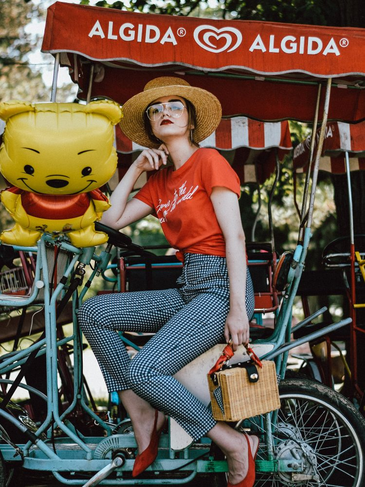 Mango high waist gingham trousers, check pants, topshop feminist t-shirt, tee, graphic tee, Zara high waist gingham pants, mango knotted feminist red tshirt, asos red graphic t-shirt, tank, red and gingham outfit, retro chic inspired summer outfit 2017, h&m straw boater hat, etsy wicker square bamboo bag, the sold out mango bamboo bag, the popular summer bag from mango, the bag you have seen everywhere on instagram, nordstrom red suede slingbacks, sling back shoes, how to wear the clear lens glasses trend, aviator glasses frames, andreea birsan, couturezilla, cute summer outfit ideas 2017, silver hoop earrings, vintage printed silk scarf, check pants, picnic, a walk in the park, winnie the pooh balloon, happy girl, the best summer bag, the feminist t-shirts trend you have seen everywhere, where to get a feminist tee from, vintage inspired 2017, fashionista, fashion inspiration, how to wear high waist gingham trousers, high waisted pants, how to knot a tee, what to wear with gingham print, where to find a straw hat, how to dress in summer 2017, ootd, outfit of the day, photos of cool tumblr girls, girl, pictures, photo, pinterest chic outfit ideas for women 2017, summer street style in europe 2017, street style, european fashion blogger, uk fashion blogger, uk fashion blog, united kingdom, silver accessories, how to look retro modern, minimal outfits for women, summer outfit ideas, inspo, inspiration, style inspiration 2017, alternatives to dresses in summer, smart casual outfit ideas for women 2017, how to wear red like a pro, red lipstick