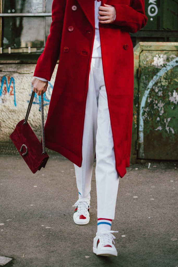 H&M red coat, red fedora wool hat, mango white peg trousers, tappered trousers trend, white pants, wide leg pants in white, how to wear wide leg trousers like a pro, how to mix sporty clothes with formal ones, red suede gucci dionysus bag, gucci lookalike bag, gucci ace heart embroidered sneakers, gucci sneakers in white, gucci leather shoes, the sold out asos 90s small cat eye sunglasses, retro sunglasses trend, where to find the best micro sunglasses, boohoo white sweatshirt with a message, andreea birsan, couturezilla, cute winter outfit ideas for 2018, how to wear red and white in a winter outfit, red and white outfit, winter outfit editorial, the red coat you need for valentine's day, v-day, vday, edgy outfit, how to look Parisian chic, European summer street style inspiration for women 2017, pinterest chic outfit ideas for woman, summer outfit ideas, summer ootd inspiration, outfit of the day, ootd, fashion icon, style inspiration, fashionista, fashion inspiration, style inspo, what to wear in summer, how to look French, chic on a budget, zara outfit, mango, topshop, asos, river island, forever 21, urban outfitters, how to mix high end pieces with luxury ones, zara and Gucci,outfit alternatives for summer, tomboy chic, minimal outfit, tumblr girls photos, pictures, happy girl, women, smart casual outfits, the best outfit ideas 2017, what to wear when you don't feel inspired, summer in Europe, weekend attire, uniform, French women in summer, European outfit ideas 2017, minimal chic outfit, how to stand out, the best outfit ideas for summer, the sunglasses you have seen everywhere on Instagram, glasses, uk fashion blogger, united kingdom, uk fashion blog, fashion and travel blog, Europe, women with style, street style, summer fashion trends 2017, best fashion ideas, styling, fall fashion, fall outfit, fall ootd, fall perfect, transitional dressing, best transitional outfit ideas, how to wear statement earrings, dressing for autumn, autumn outfit, winter outfit ideas for work and school 2017, silver hoop earrings, red lipstick, low ponytail with hat