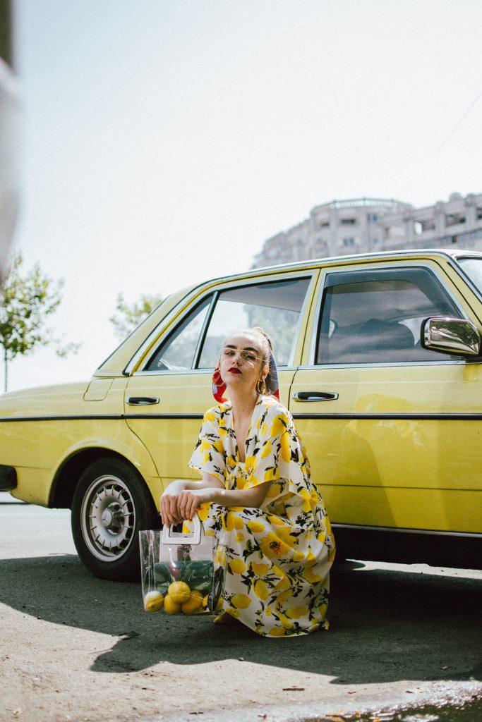Lemon print midi dress, yellow slingback shoes, transparent tote bag, andreea birsan, couturezilla, cute summer outfit ideas 2018, lemon print dress, tie front lemon print dress, sicialian print, why you should wear a fruit print this summer, the prints that are hot right now, the best holiday dress, what you should wear on a summer holiday, warm weather midi dress, yellow and white midi tie front dress, top knot dress, vinyl tote bag, staud inspired bag, how to wear yellow, lemons, fruit print clothing, d&g inspired print dress, lemon printed dress, how to wear a midi dress, what shoes to wear with a midi dress, yellow suede slingback shoes, yellow kitten heel shoes, slingbacks, yellow shoes, how to pull off yellow shoes, the transparent bag trend, pcv bag, celine inspired plastic bag trend, the best bags from mango, silk striped scarf, scarf in hair, how to style a scarf in your ponytail, how to wear a scarf, best summer dresses, how to look Parisian chic, European summer street style inspiration for women 2017, pinterest chic outfit ideas for woman, summer outfit ideas, summer ootd inspiration, outfit of the day, ootd, fashion icon, style inspiration, fashionista, fashion inspiration, style inspo, what to wear in summer, how to look French, chic on a budget, zara outfit, mango, topshop, asos, river island, forever 21, urban outfitters, how to mix high end pieces with luxury ones, zara and Gucci,outfit alternatives for summer, tomboy chic, minimal outfit, tumblr girls photos, pictures, happy girl, women, smart casual outfits, the best outfit ideas 2017, what to wear when you don't feel inspired, summer in Europe, weekend attire, uniform, French women in summer, European outfit ideas 2017, minimal chic outfit, how to stand out, the best outfit ideas for summer, the sunglasses you have seen everywhere on Instagram, glasses, uk fashion blogger, united kingdom, uk fashion blog, fashion and travel blog, Europe, women with style, street style, summer fashion trends 2017, best fashion ideas, styling, fall fashion, fall outfit, fall ootd, fall perfect, transitional dressing, best transitional outfit ideas, how to wear statement earrings, dressing for autumn, autumn outfit, winter outfit ideas for work and school 2017, clear lens aviator glasses, the clear lens glasses trend, geeky glasses, gold hoop earrings